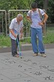 L'uomo anziano sta scrivendo i caratteri di Han sulla terra con la spazzola ed acqua Fotografia Stock Libera da Diritti