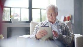 L'uomo anziano sta utilizzando il computer della compressa a casa stock footage