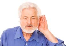 L'uomo anziano tiene la mano sull'orecchio immagini stock