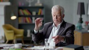 L'uomo anziano triste e disturbato infelice esamina incredulously una pillola e la prende stock footage