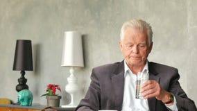 L'uomo anziano triste e disturbato infelice esamina una pillola e la prende archivi video