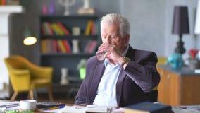 L'uomo anziano triste e disturbato infelice esamina una pillola e la prende stock footage