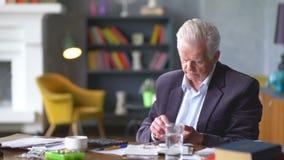 L'uomo anziano triste e disturbato infelice esamina una pillola e riflette archivi video
