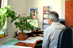 L'uomo anziano, un ragioniere, si siede in ufficio e negli impianti con il computer Sulla tavola sono molti documenti Immagine Stock