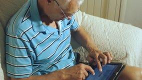 L'uomo anziano utilizza la compressa stock footage