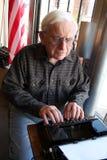 L'uomo anziano utilizza la macchina da scrivere Immagini Stock Libere da Diritti