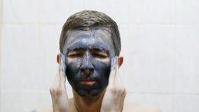 L'uomo applica la maschera crema nera sul fronte contro acne video d archivio