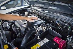 L'uomo apre il cappuccio dell'automobile e l'automobile di lucidatura con il panno del microfiber Fotografie Stock