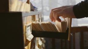 L'uomo apre il cassetto della base di dati Il giovane bibliotecario apre l'indice di carta delle biblioteche Archivio, base di da stock footage