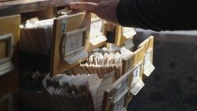 L'uomo apre il cassetto della base di dati Il giovane bibliotecario apre l'indice di carta delle biblioteche Archivio, base di da archivi video