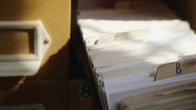 L'uomo apre il cassetto della base di dati Il giovane bibliotecario apre l'indice di carta delle biblioteche Archivio, base di da video d archivio