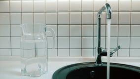 L'uomo apre il rubinetto ed il flusso dell'acqua versa nel lavandino all'interno stock footage