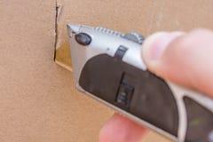 L'uomo apre una scatola con un coltello del mestiere fotografie stock
