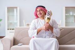 L'uomo arabo con il premio e soldi sul sofà Fotografie Stock