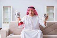 L'uomo arabo con il premio e soldi sul sofà Fotografie Stock Libere da Diritti