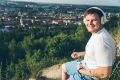L'uomo ascolta musica sul picco della collina Fotografia Stock