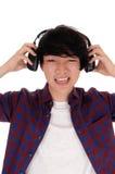 L'uomo asiatico ascolta musica Immagine Stock