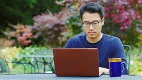 L'uomo asiatico che indossa i vetri lavora con un computer portatile Sedendosi sul terrazzo di estate nei giardini o nei caffè archivi video