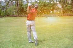 L'uomo asiatico dei giocatori di golf ha colpito il campo da golf ampio nell'estate Fotografia Stock