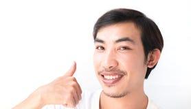 L'uomo asiatico del primo piano che mostra i pollici su con il fondo bianco, eccelle Fotografie Stock Libere da Diritti