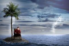 L'uomo asiatico di affari si siede sulla sedia, sola sulla piccola isola Fotografie Stock
