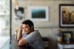 L'uomo asiatico ha un dubbio e pensa in una caffetteria fotografia stock libera da diritti