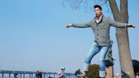 L'uomo asiatico impara equilibrare e camminare su una corda allungata fra gli alberi in un parco della città Uomo che equilibra e archivi video