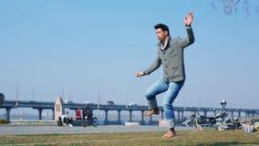 L'uomo asiatico impara equilibrare e camminare su una corda allungata fra gli alberi in un parco della città Uomo che equilibra e video d archivio