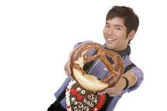 L'uomo asiatico in Lederhose tiene la ciambellina salata di Oktoberfest Immagini Stock