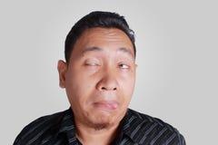 L'uomo asiatico mostra l'espressione facciale potabile ridicola Fotografie Stock