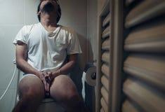 L'uomo asiatico sta sedendosi sulla toilette Immagini Stock Libere da Diritti