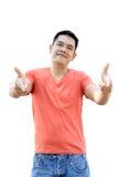 L'uomo asiatico sta stando nell'indicare anteriore sul fondo bianco Fotografia Stock