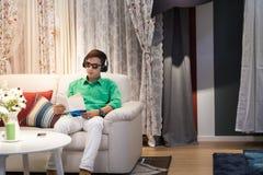 L'uomo asiatico in vestito casuale con i vetri di sole ed il trasduttore auricolare si siedono sulla s Immagine Stock Libera da Diritti