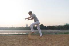 L'uomo atletico casuale si prepara per saltare sulla spiaggia mentre allenamento Fotografia Stock