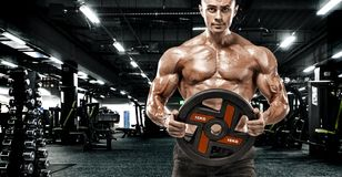 L'uomo atletico del forte culturista muscolare brutale che pompa su muscles il fondo di concetto di culturismo di allenamento - b immagini stock