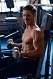 L'uomo atletico di potere bello nell'addestramento che pompa su muscles con Fotografia Stock Libera da Diritti