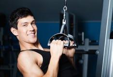 L'uomo atletico risolve sulla strumentazione di ginnastica di forma fisica Immagine Stock