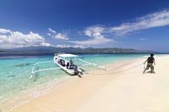 L'uomo attracca la barca ancorata sulla spiaggia tropicale Fotografie Stock Libere da Diritti