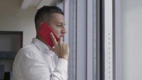L'uomo attraente in camicia bianca parla sullo smartphone vicino alla finestra in ufficio stock footage