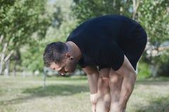 L'uomo attraente che fa l'allungamento si esercita all'aperto in parco Immagini Stock