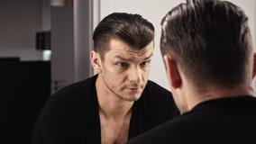 L'uomo attraente davanti ad uno specchio in una camicia nera si esamina archivi video