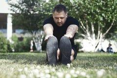 L'uomo attraente in sportwear nero che fa l'allungamento si esercita all'aperto in parco Immagine Stock Libera da Diritti