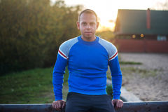 L'uomo attraente sta sulla spiaggia nel tramonto di sera dopo lo sport Fotografie Stock Libere da Diritti