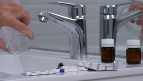L'uomo in bagno versa un vetro con acqua nel lavandino dopo che prende le pillole mediche archivi video