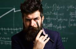 L'uomo barbuto è istitutore o insegnante Attività connesse con l'istruzione in aula alla scuola L'istitutore dovrà rivalutare fotografia stock libera da diritti