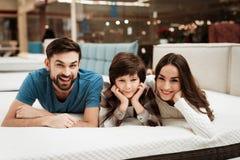 L'uomo barbuto adorabile, insieme alla suoi bei moglie e figlio, si rilassa sul materasso nel deposito immagini stock