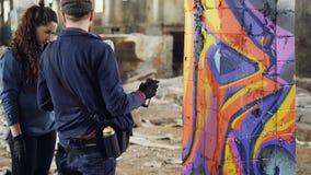 L'uomo barbuto bello dell'artista urbano sta insegnando allo studente dilettante a lavorare con la pittura dell'aerosol mentre de video d archivio