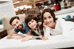 L'uomo barbuto bello, insieme alla suoi bei moglie e figlio, si rilassa sul materasso nel deposito immagine stock
