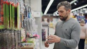 L'uomo barbuto bello sta scegliendo la griglia della griglia in supermercato, sta tenendolo che controlla la qualità ed il prezzo stock footage