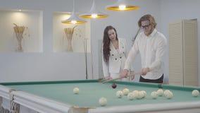 L'uomo barbuto biondo insegna alla sua amica a giocare il biliardo L'uomo sicuro in camicia bianca spiega alla donna in elegante video d archivio